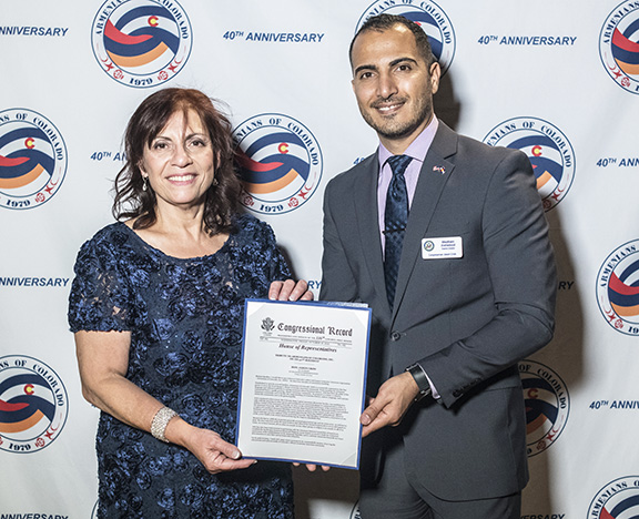 AOC Board President Sona Hedeshian (left) and Congressman Jason Crow's District Director Maytham Alshadood hold the Congressional Record Tribute in celebration of the 40th anniversary of AOC (Photo by Evan Semón)
