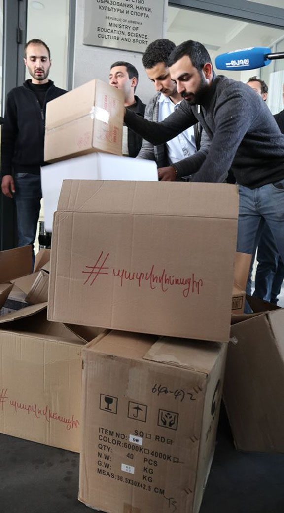 Members of the ARF Youth of Armenia carry moving boxes to Education Ministry as a protest demanding the minister's resignation