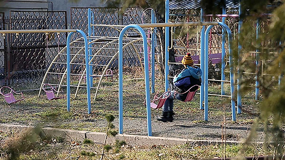 A boy sits on a swing in the courtyard of an orphanage for children with disabilities, Yerevan, Armenia. © 2016 Alexei Golubev for Human Rights Watch
